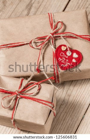 silver gift box with vinous bow on wooden background - stock photo