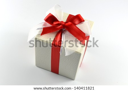 Silver gift wrapped present with red satin bow isolated on white - stock photo