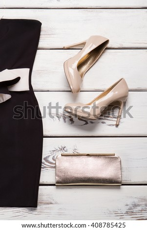 Silver handbag and strapless dress. Golden clutch bag on showcase. Lady's high-quality accessory. New evening purse on sale. - stock photo
