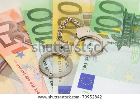 silver handcuffs on many large euro notes - stock photo