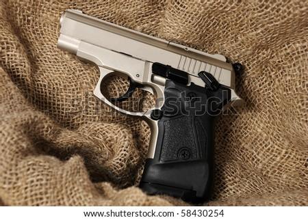 Silver handgun on burlap background - stock photo