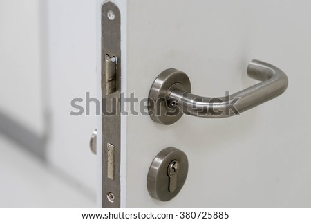 silver handle on white door and locksmith - stock photo