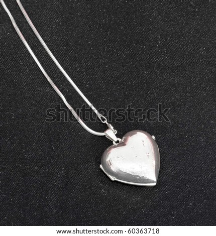Silver heart closed - jewelery on black background - stock photo