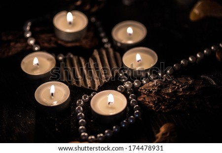 Silver heart surrounded by candles and silver beads - stock photo
