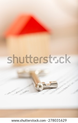 Silver house key lying on a contract for purchase, lease, insurance or mortgage in a real estate concept, viewed low angle with focus to the tip. - stock photo