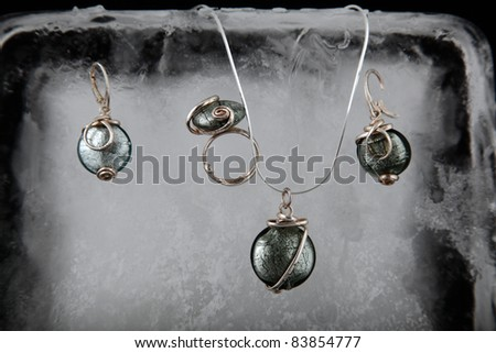 Silver jewelry with beautiful glass on icy background