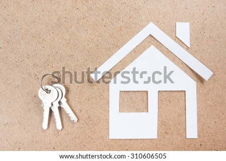 Silver key with house figure and on wooden background. Real Estate Concept. Top view. - stock photo