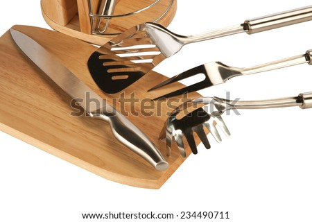 Silver kitchen utensils including whisk, tong and spoon on a white background and knife set - stock photo