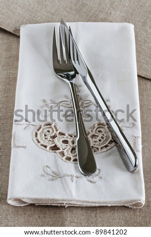 Silver knife and fork on vintage embroidered linen