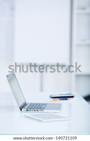Silver laptop and tablet on white table - stock photo