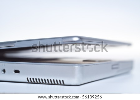 silver laptop side-view fading out on white laptop closing lid - stock photo