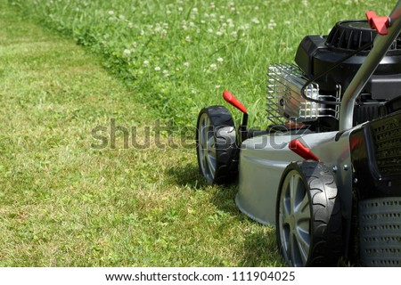Silver lawn mower in the garden. - stock photo