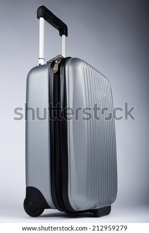 Silver luggage, suitcase, gray gradient backgound - stock photo