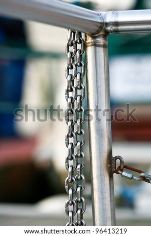 silver metal chains hanging from silver metal railings - stock photo