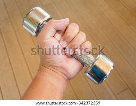 silver metal dumb bells in human hand over wooden background - stock photo