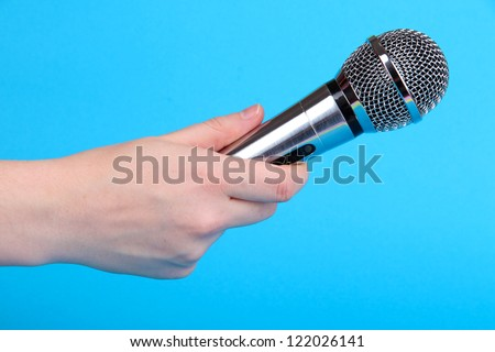 Silver microphone in hand on blue background - stock photo