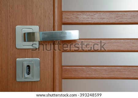 Silver, modern door handle on brown wooden door with milky white translucent glass