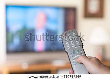 Silver modern TV remote control being pressed by thumb with out of focus screen background - stock photo