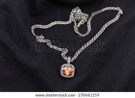 Silver necklace with a pendant on a black fabric - stock photo