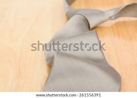 Silver necktie on wooden table background
