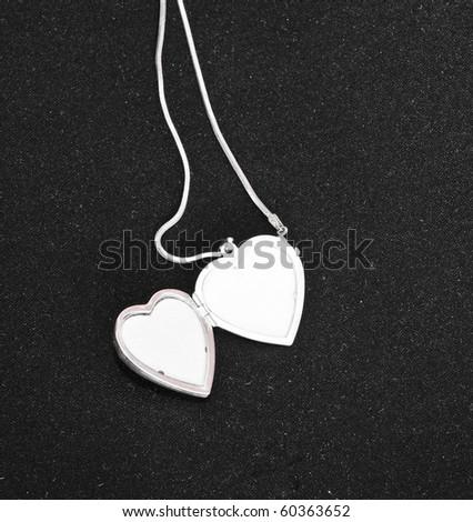 Silver opened heart on black background, jewelery - stock photo