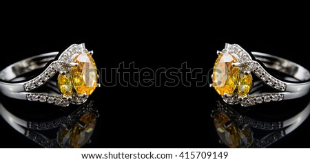 Silver or white gold rings with yellow gems and diamonds on black glass background with space for your text - stock photo