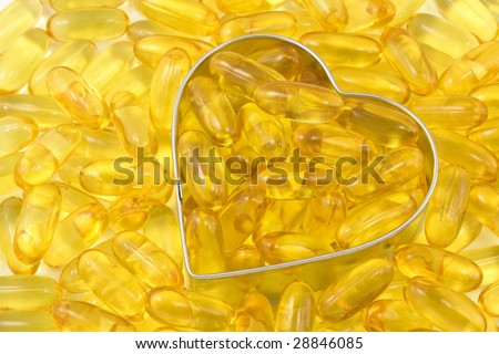 silver outlined heart filled and surrounded by salmon oil - stock photo
