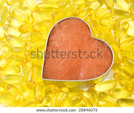 silver outlined salmon heart surrounded by salmon oil - stock photo