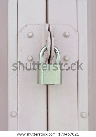 Silver padlock on pink metal door  - stock photo