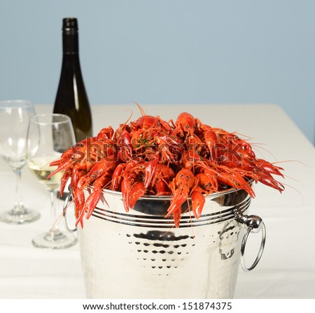 silver pail full of river lobster with wine and glasses on white table linen. - stock photo