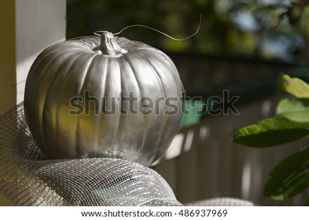 Silver painted pumpkin on a fence still life for fall with copy space and a shallow depth of field