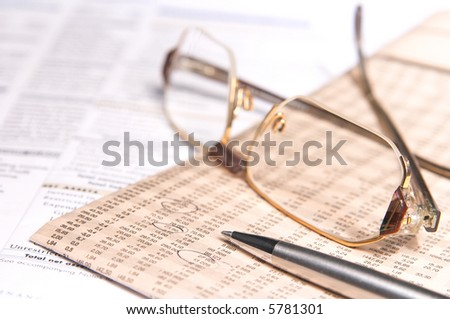 Silver pen and eyeglasses on top of financial newspaper; Focus on the pen's tip.