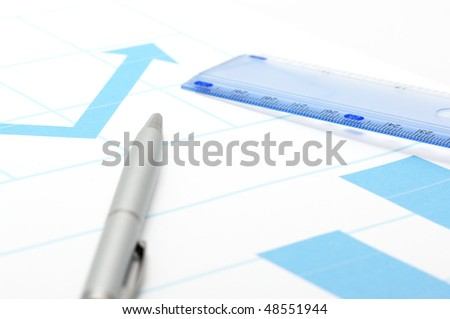 Silver pen and rule on page with blue graphs.