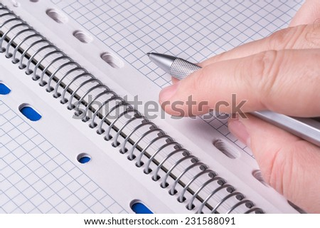 silver pen in hand on open math agenda - stock photo