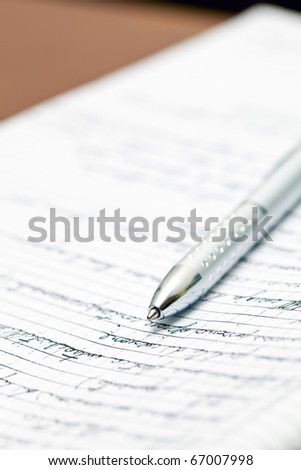 Silver pen lying on a notebook in the office - stock photo