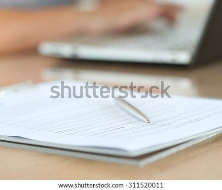 Silver pen lying on document pad while female hands working on notebook pc in background. Office life, paperwork, client contract, business agreement concept. Focus on pen - stock photo