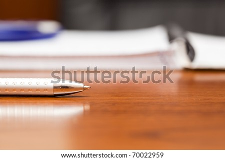 Silver pen on the table near a notebook - stock photo