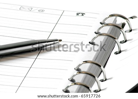Silver pen on white address book, white background