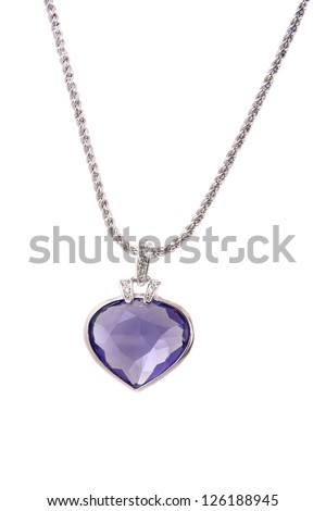 Silver pendant and blue heart shaped diamond on white background - stock photo