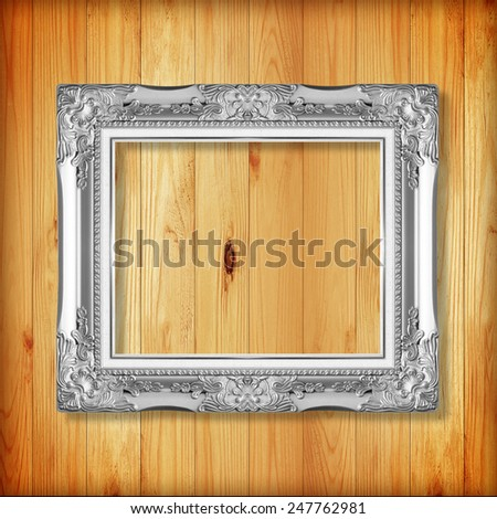 silver picture frame on wooden wall;. Empty  picture frame on wooden wall.