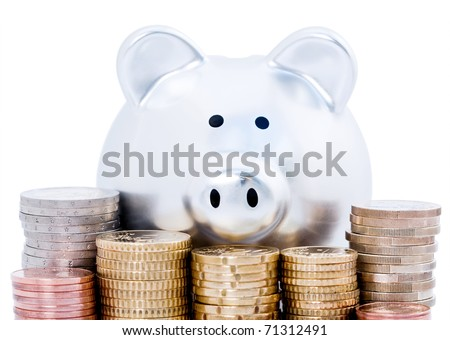 Silver piggy bank behind piles of Euro coins, isolated on white background. - stock photo