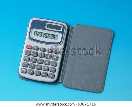Silver pocket calculator isolated on blue background.