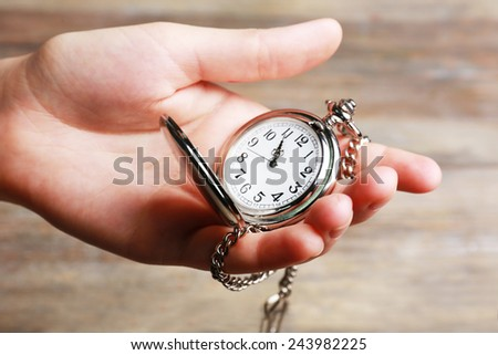 Silver pocket clock in hand on wooden background - stock photo