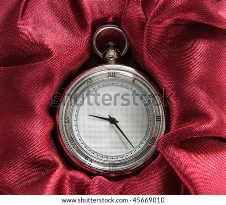 Silver pocket watch on red - stock photo