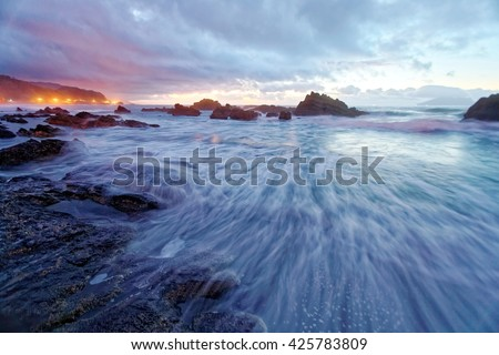 Silver rays of the moon light up the waves on Wai'ao Beach, in Ilan, Taiwan (Long Exposure Effect) ~ A beautiful beach illuminated by the first ray of morning sunshine under dramatic sky - stock photo