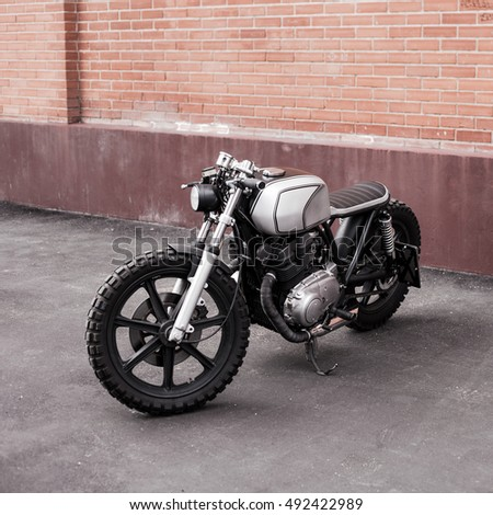 Silver rebuilt motorcycle cafe-racer parked by the wall in the empty street. Wild lifestyle