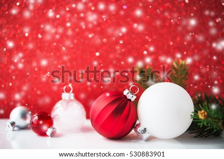 Silver, red and white christmas ornaments on red glitter bokeh background with blurred snow and xmas tree. Merry christmas greeting card. Winter holiday xmas theme. Happy New Year. Space for text.