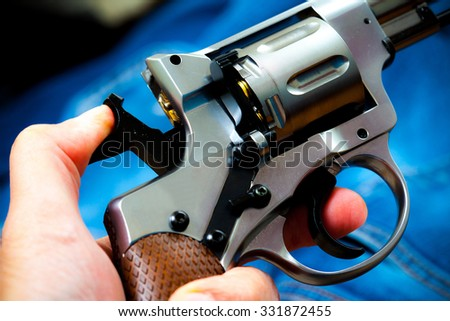 silver revolver in human hand, close up - stock photo