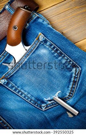 silver revolver nagant with brown handle in the pocket of old blue jeans. close up - stock photo