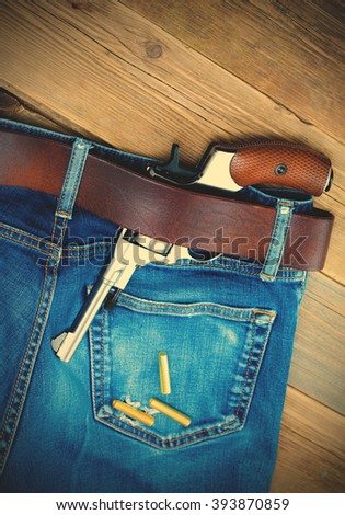 silver revolver nagant with brown handle in the pocket of old blue jeans. copy-space. close up. instagram image filter retro style - stock photo
